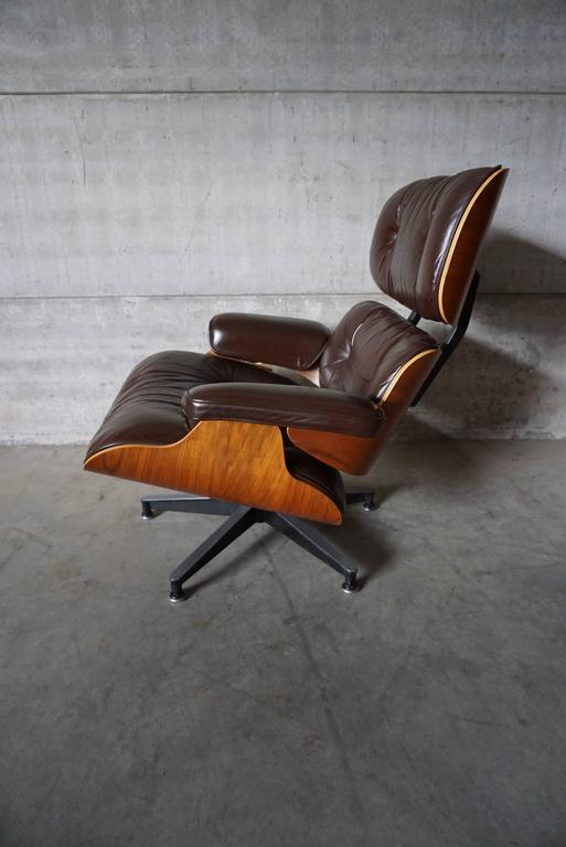 This model 670 lounge chair was designed by Charles & Ray Eames in 1956. This chair was produced in the 1990s by Herman Miller. They feature walnut veneer moulded plywood seat shells and dark brown leather-covered cushions resting on a cast