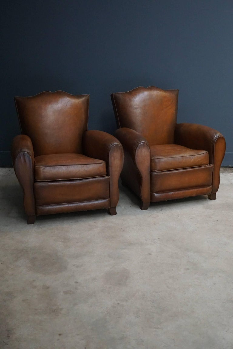 These club chairs were designed and produced in France during the 1940s. The chairs are made from cognac leather held together with metal pins and mounted on wooden legs.