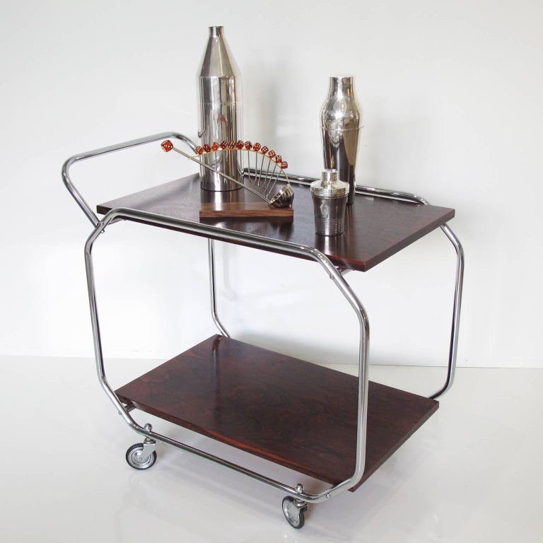 Streamlined European Art Deco rolling bar serving cart with Bauhaus modernism influenced design. Featuring chromed metal round tubing frame with rosewood upper and lower shelf. Chrome push/pull handle and four original wheels in perfect working