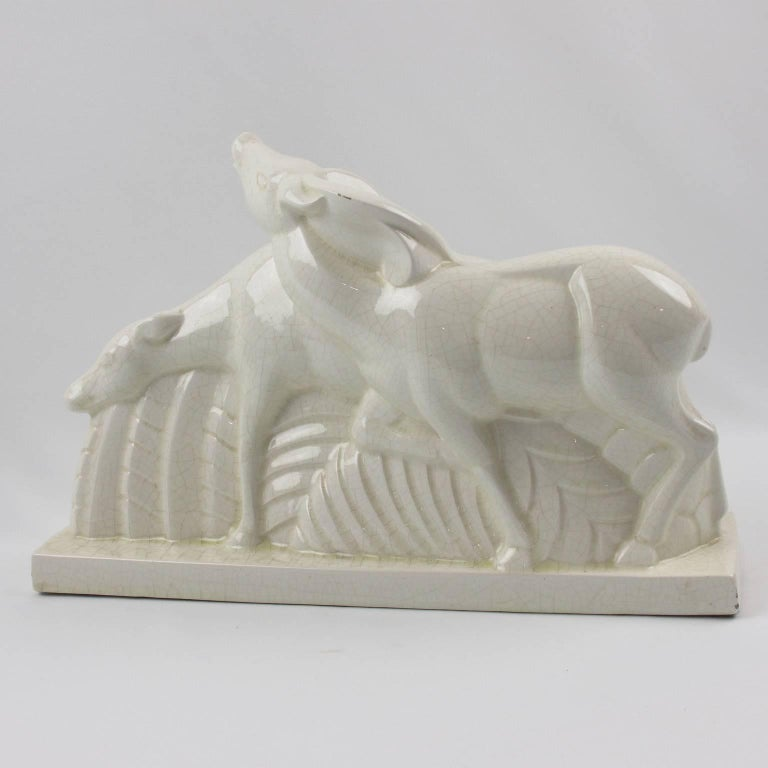 Designed by Charles Lemanceau (1905 - 1980) and made by Manufacture de Faiences d'Art de Saint-Clement this typical Art Deco crackle glaze ceramic sculpture features a pair of deer or antelopes or does. The sculpture is signed on edge of base: