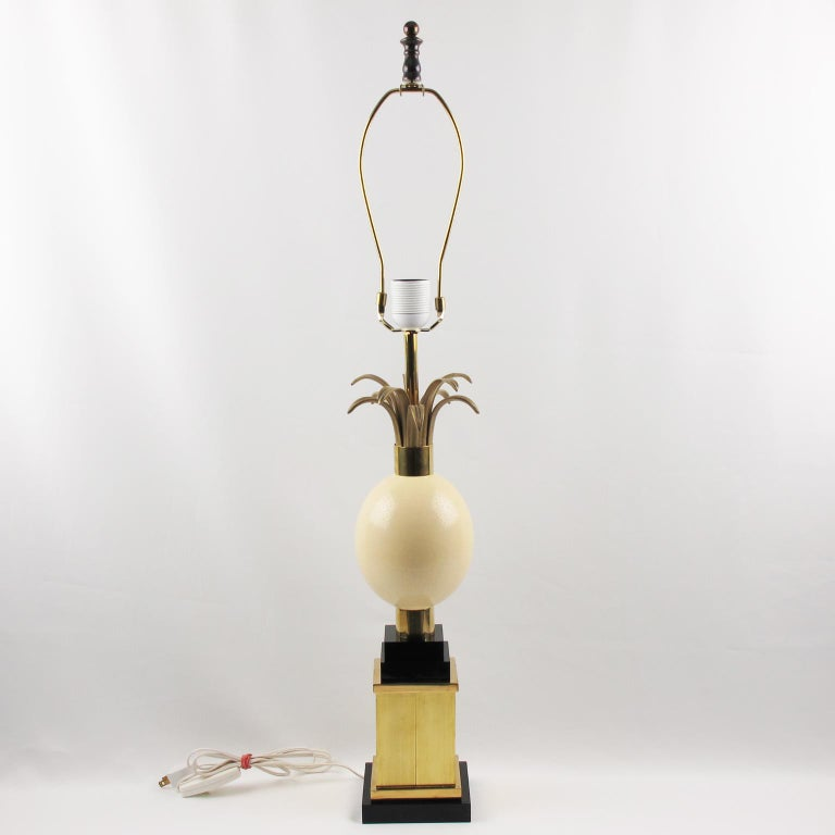 Elegant chic tall table lamp attributed to Maison Charles et Fils, France. Featuring a large ostrich egg topped with gilded metal fronds on gilded brass and black Lucite pedestal base. Rewired to fit US standard. No shade included. Measurements: