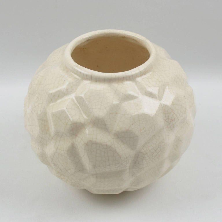 Lovely Art Deco vase by Faiencerie Saint Clement, France. French ceramic vase with white crackle glaze finish. Features a large puffy round shape with large collar opening and detailed stylized carving with geometric shape all around. The crackle