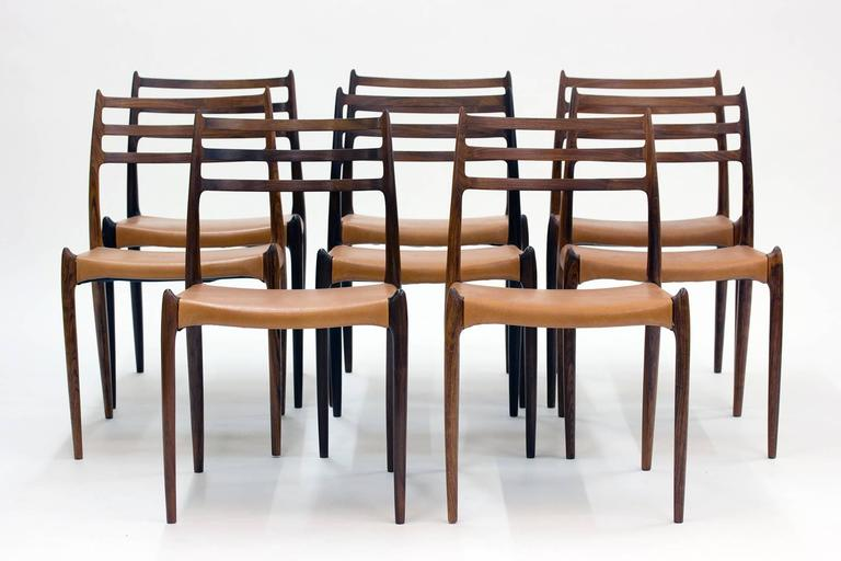 Set of eight gorgeous rosewood dining chairs by Niels O. Møller. Model 78 designed in 1962.  Vintage leather seats in a tan nuance. The fluency of the design and the hornlike details at the seats and on the backrests give these chairs a breathtaking