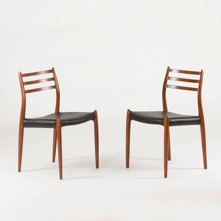 Set of eight beautiful dining chairs by Niels O. Møller, made of teak with black leather seats. Sculptural, hornlike details on the backrest and where the legs meet the seat. Wonderful quality, execution and comfort.