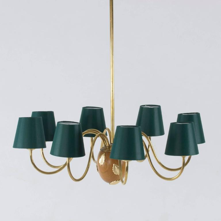 Vivacious brass chandelier with eight arms by Hans Bergström. The center of the chandelier is an acorn-shaped mahogany piece, decorated with beautiful brass leaves. Brass pole and cup.