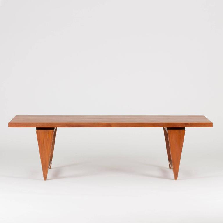 Coffee table by Illum Wikkelsø made from solid teak. Edgy details and a tabletop that seems to hover just above the base.