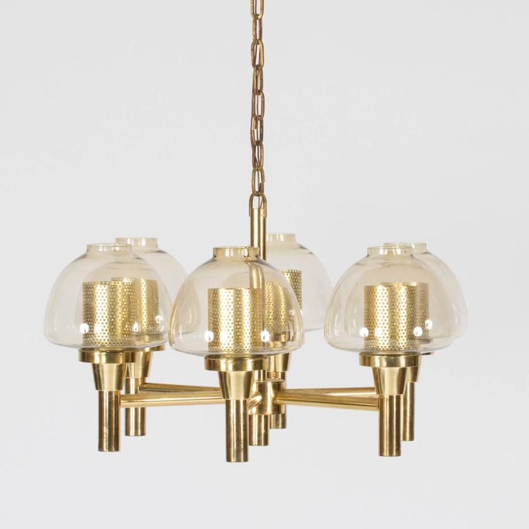Brass and smoke-colored glass chandelier by Hans-Agne Jakobsson. Inner shades around the light bulbs, cylindrical in shape with small holes that let out the light in a beautiful way. The chandelier hangs on a chunky brass chain that measures 100 cm.