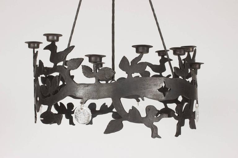 Amazing wrought iron chandelier by the artist Bertil Vallien. Thick circular glass spheres hanging like pendants alternating with the cut-out decor of fish, leaves, birds and cherubs. Twelve tea light holders are mounted along the top edge. The