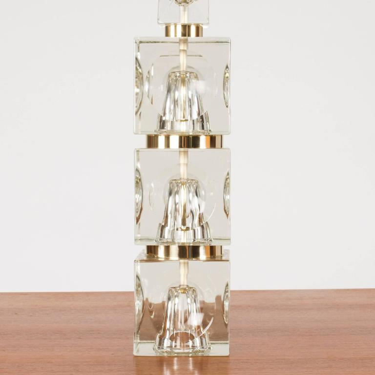 Awesome Swedish 1960s crystal table lamp. Chunky base of stacked cubes with concave spherical cuts creating an interesting visual effect. The spaces between the cubes are painted gold.