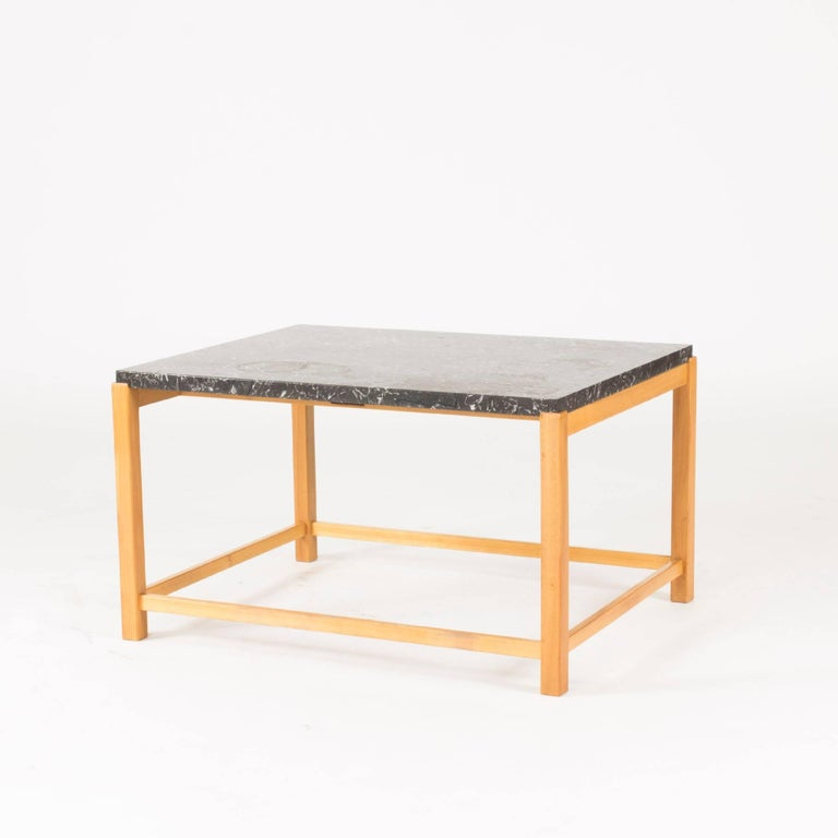 Very cool coffee or occasional table with a strict, open Silhouette and wonderful, lively black marble top. Elmwood base.