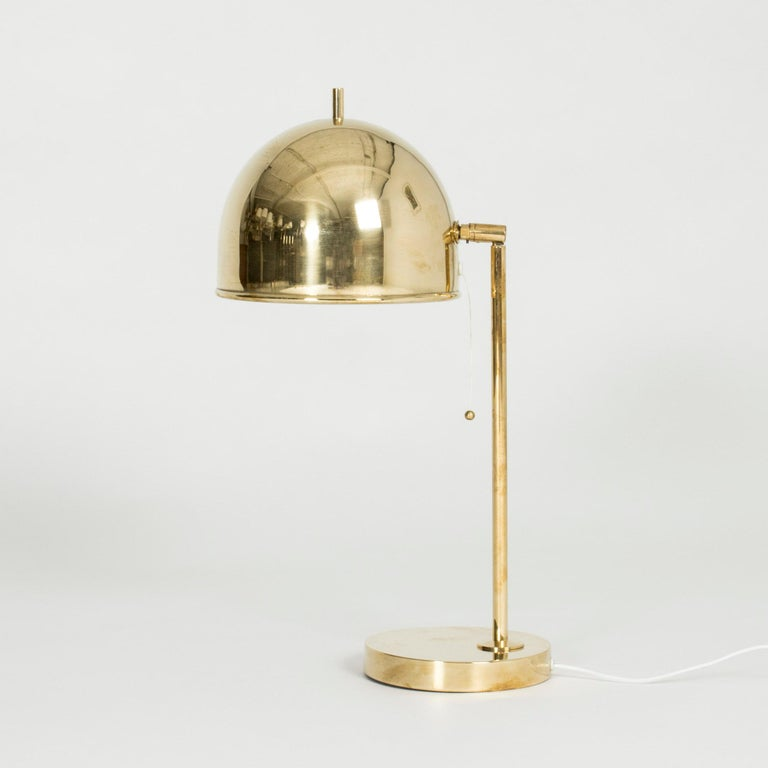 Brass table lamp from Bergboms in a design that combines the generous arch of the shade with strict lines. The little tip on the top of the shade adds a whimsical look.