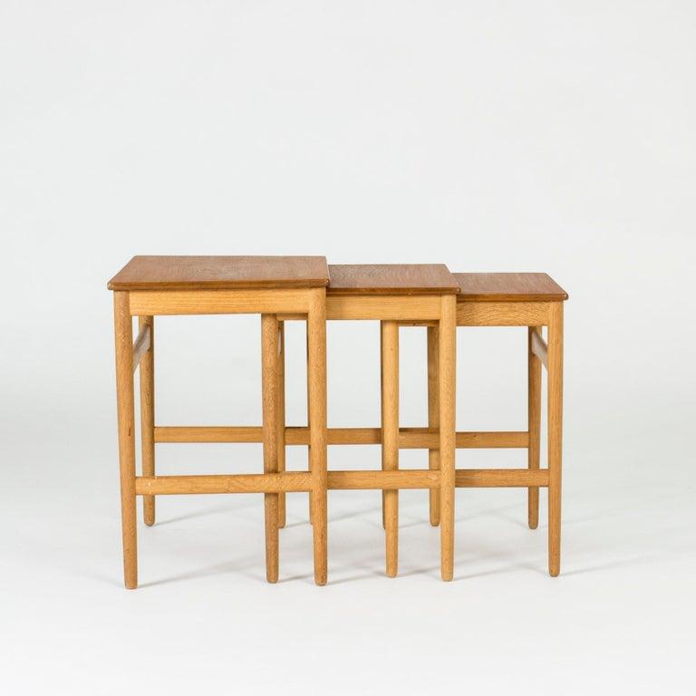 Set of three neat, sleek nesting tables by Hans J. Wegner. Oak legs with teak table tops.
