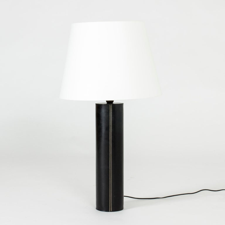 Large table lamp from Swedish lighting firm Bergboms with cylindrical base dressed in black leather decorated with white seams – a Minimalist design with a deluxe finish.