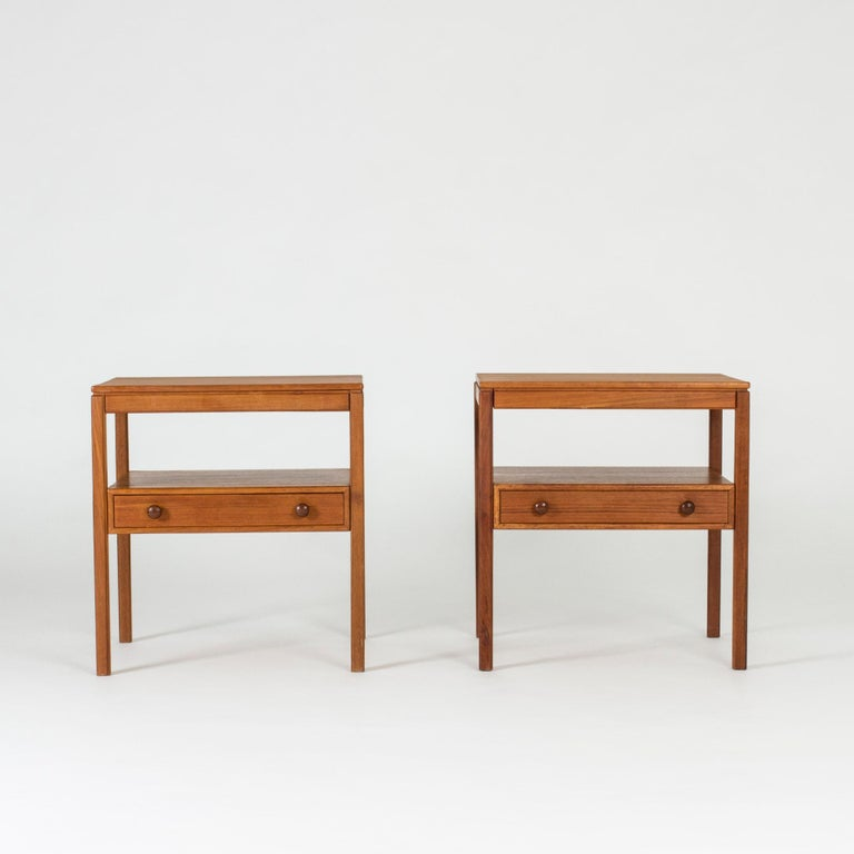 Pair of cool bedside tables by Sven Engström and Gunnar Myrstrand, made from teak. Drawers with decorative knob handles.