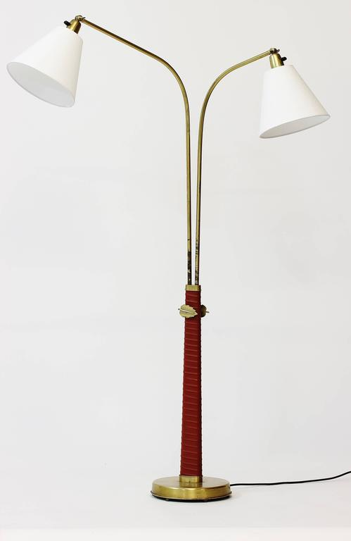 A pair of rare and exceptional floor lamps by Hans Bergström. Made in brass and red leather. Adjustable height with the massive brass leaves working as stoppers. This pair is from his early 1930s production and one of the most beautiful Swedish