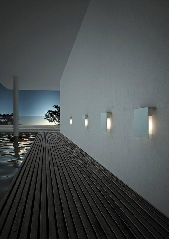 Designed by David Chipperfield in 2008 and manufactured by Fontana Arte, the Corrubedo outdoor wall lamp is structured in stainless steel with the diffuser in opaline white polycarbonate with a transparent borosilicate glass shield. The lamp comes