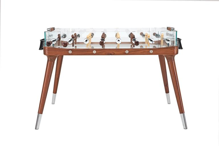 A subtle and elegant walnut structure highlights and supports this modern and essential foosball table, inviting the challenge of enjoying the game until its very last minute (90° Minuto). Engineering and technology is cleverly concealed beneath the