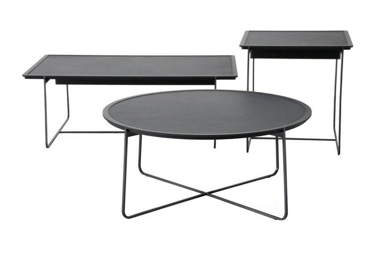 """""""Petit Cuvee"""" is a low round side table, designed by Stephane Lebrun and manufactured by Dessie', featuring a top in black MD walnut veneered or covered by black leather and a metallic base structure made of square section steel with an"""