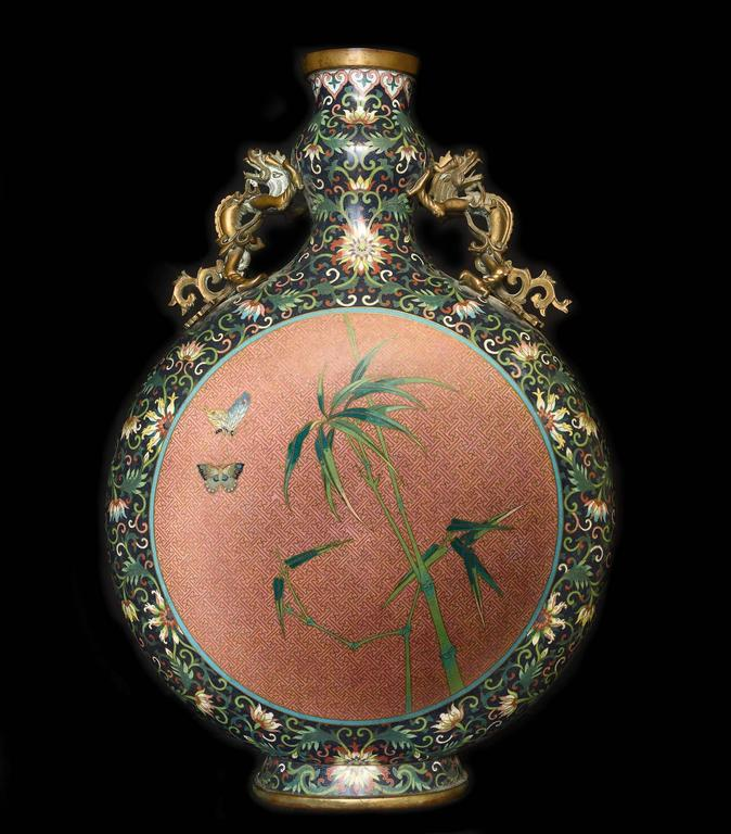 A 19th century Chinese moon flask, in cloisonné́ metal with dragon-shaped handle, floral decorations and peonies in the circle, wooden base.