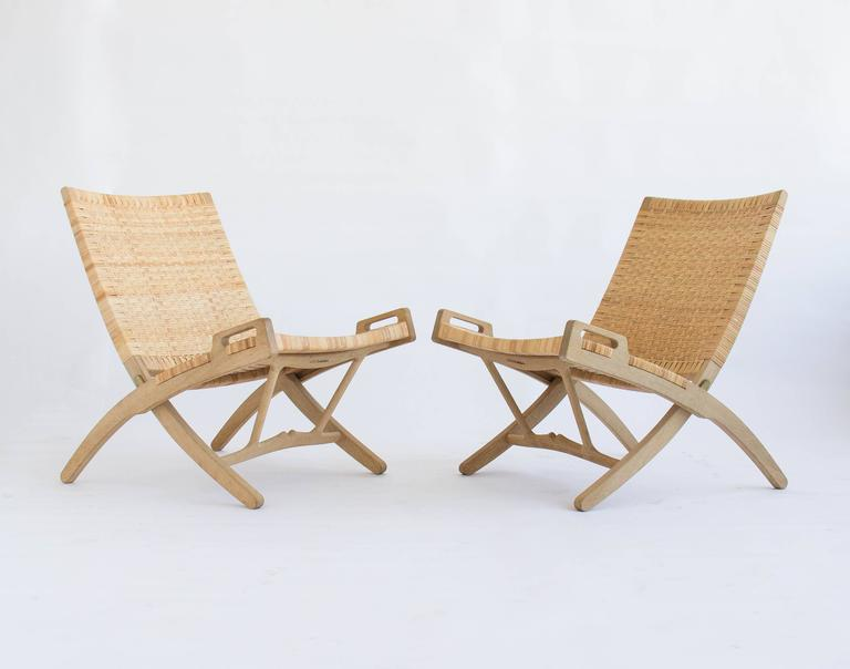 Pair of folding lounge chairs made by PP Møbler in 2007. The pair was designed by Hans Wegner in 1949. For many years this design was produced by Johannes Hansen.  Each chair includes oak wall hook so the chairs can be hung while not in