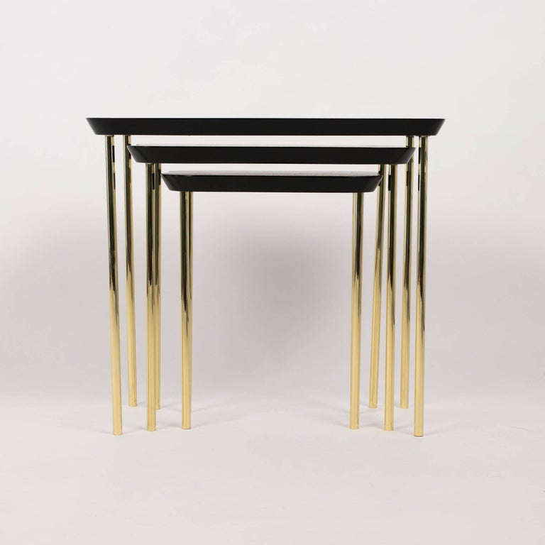 A set of three modernist nesting tables from Boston's Charak modern. Charak pieces are distinguished by their transitional qualities, and these modern pieces are also in conversation with Hollywood Regency and Art Deco silhouettes. The largest table