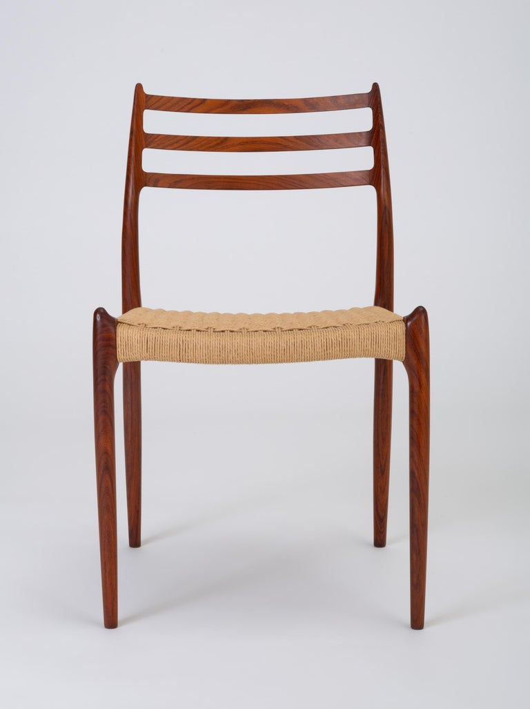 A set of six rosewood dining chairs designed by Niels Otto Møller in 1962 and manufactured by JL Møllers Møbelfabrik of Denmark with Danish [paper] cord seats. The chairs have a curved backrest with three horizontal supports, terminating in a