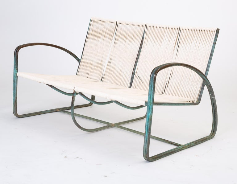 A patio settee or loveseat by Walter Lamb for Brown Jordan. An exceptionally rare example, this piece has a deep seat woven from waxed cotton sailcord around an oxidized bronze frame. The seat is suspended between two broadly arced armrests in a