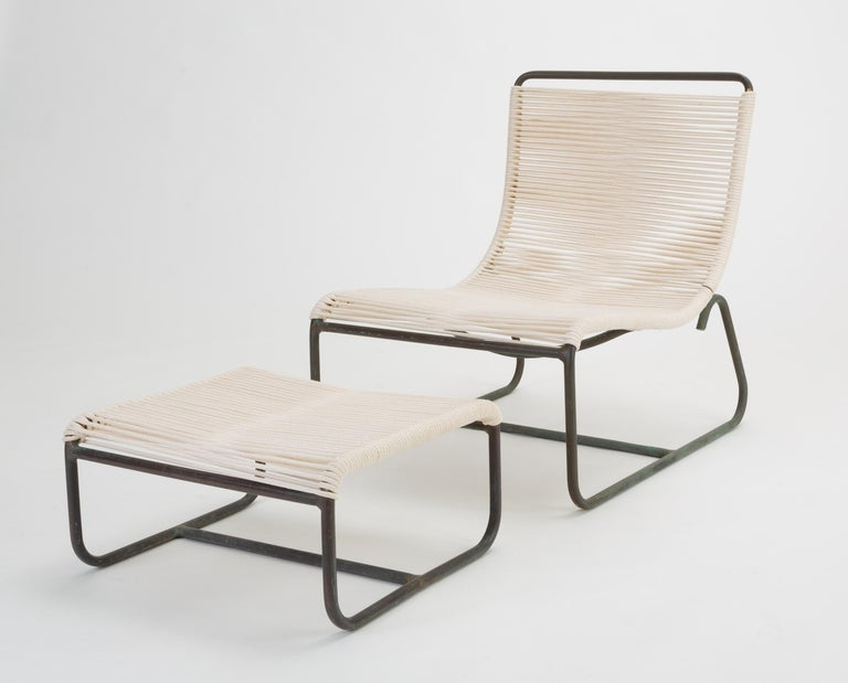 """A pair of low lounge chairs, known as the """"Sleigh Chair"""" by Walter Lamb for Brown Jordan. The pair comes with a single ottoman that slides beneath the chair seat for easy storage. A continuous length of tubular bronze serves as the frame of a"""