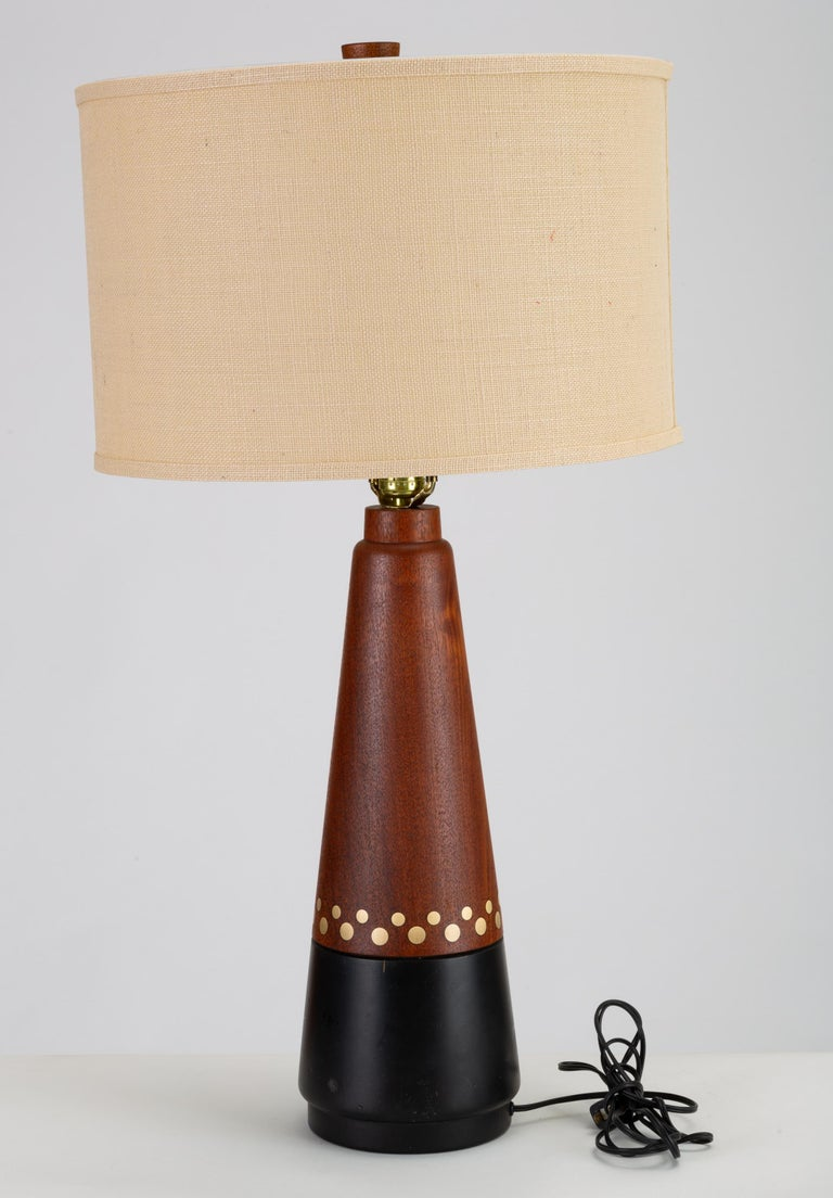 A large Danish Modern table lamp with a conical base in turned teak. Composed of two contiguous segments, the lower third of the lamp is painted black. A stylistic border of inlaid brass coins in two sizes encircles the base. Sold with the pictured