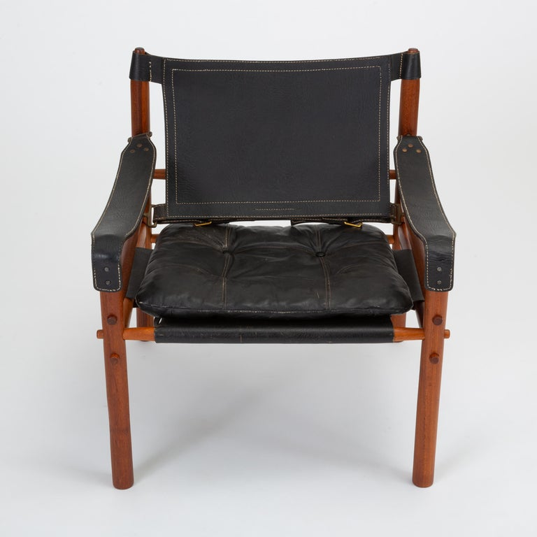 A pair of 'Sirocco' safari chair designed by Arne Norell for his eponymous company, Norell Möbel AB of Småland, Sweden. This pair features a solid teak frame strapped together by leather slings with brass fittings and black leather with contrast