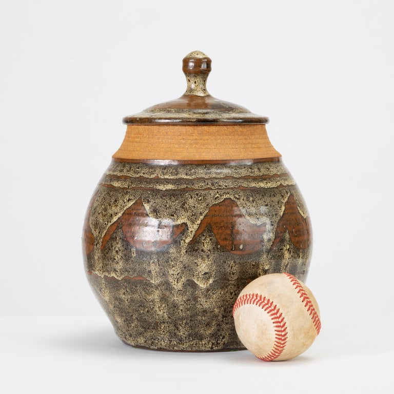Don Jennings, a prominent local ceramicist based in orange County, California, worked as instructor and artist throughout the 1960s and 1970s. This example is a wheel-thrown ceramic lidded jar with an abstract pattern in high-gloss glaze - a