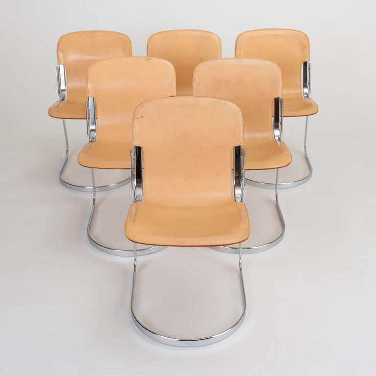 A set of six 1970s dining chairs by Willy Rizzo for Italian manufacturer Cidue. The frame of the chair is formed by two interlocking curves in flat-bar steel with a chrome finish. The seat, a chrome-plated ellipse, has a fawn-colored leather seat