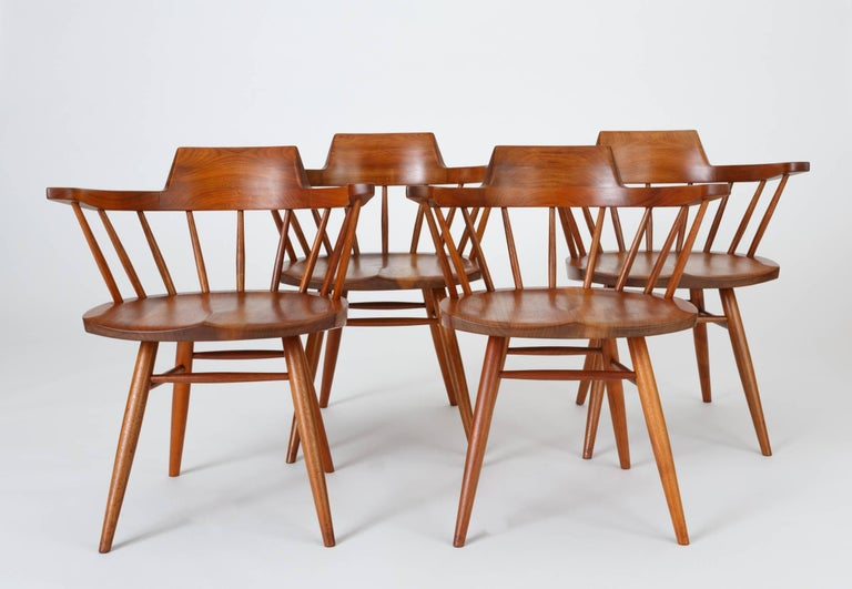 An accomplished set of four captain chairs from American midcentury craftsman George Nakashima. The black walnut chair has a curved, peaked backrest atop carved spindles, inspired by the Windsor chair and Shaker pieces. The seat is hand-sculpted for