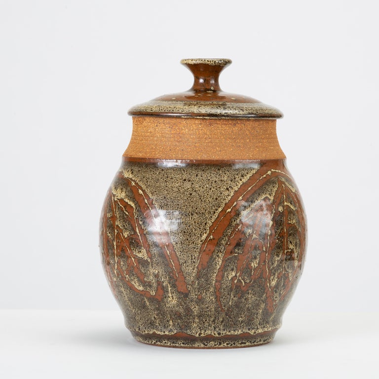 Don Jennings, a prominent local ceramicist based in Orange County, California, worked as an instructor and artist throughout the 1960s and 1970s. This example is a wheel-thrown ceramic lidded jar with a painted leaf pattern in high-gloss glaze - a