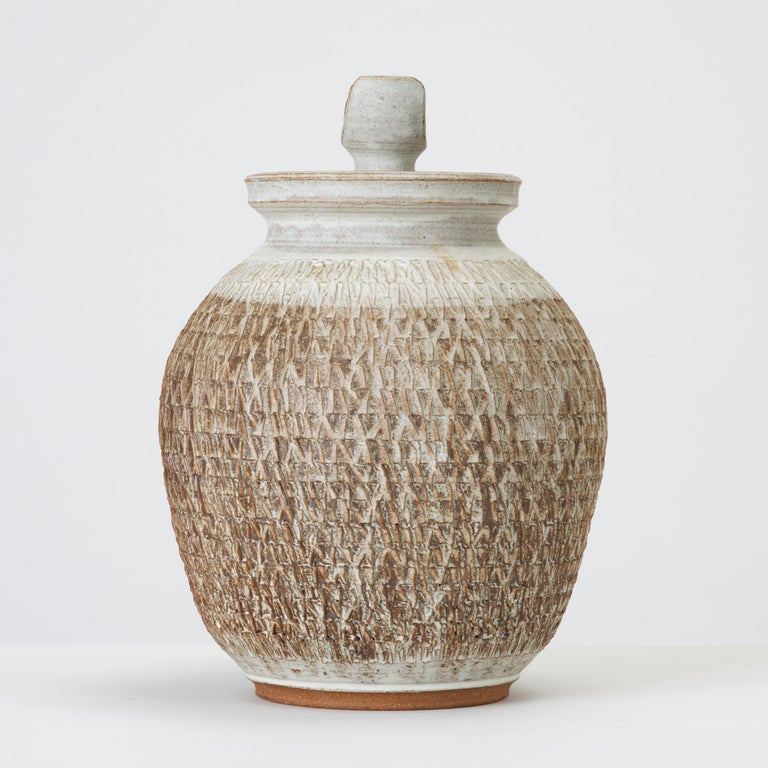 Don Jennings, a prominent local ceramicist based in Orange County, California, worked as an instructor and artist throughout the 1960s and 1970s. This example is a wheel-thrown ceramic lidded jar with a pleasing neutral palette of bone and chestnut