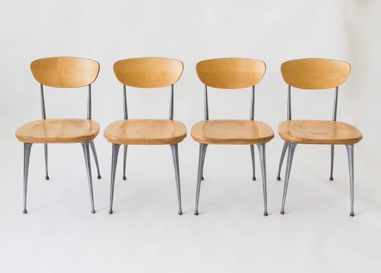 A set of four American made dining chairs from notable hospitality furniture manufacturer Shelby Williams. The gazelle-leg chair features aluminum legs cast in a proprietary design with arched back legs. The seats are solid birch and the slightly