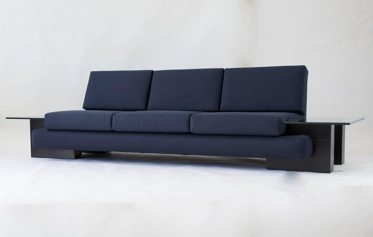 From midwestern manufacturer Kroehler, this sofa from 1978 has a rounded, upholstered frame in Oxford blue cotton. The platform sits on four molded wood blocks with an ebonized finish, and a built-in end table of thick-cut glass is mounted on either