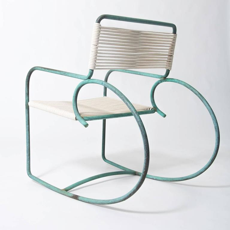Walter Lamb's patio rocking chair, produced by Brown Jordan. The chair has a sculptural shape, with a single formation of tubular bronze forming the backrest, arms, and exaggerated round runners. The back and seat are strung with cotton rope,