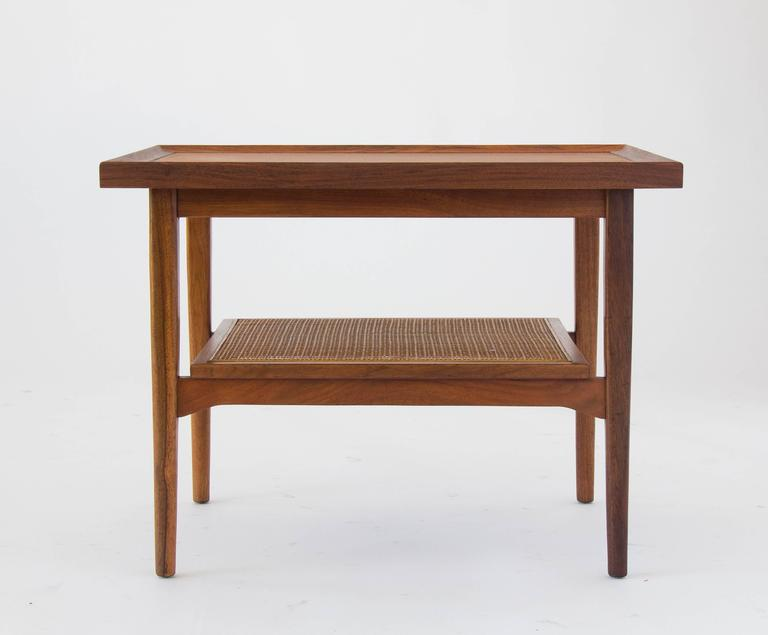 A rectangular side table from Kipp Stewart and Stewart MacDougall's iconic Declaration collection for Drexel. The walnut tabletop is framed on all sides by end pieces of solid walnut, that create a graduated lip. A smaller shelf with a walnut frame
