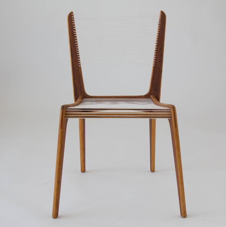 A single accent chair by French Canadian designer Jacques Guillon. Designed in 1953, the deceptively simple design consists of three interlocking wooden pieces - stacked maple faced with a contrasting walnut veneer - joined by a wooden dowel, and