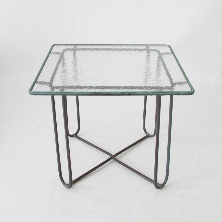 A small patio dining or card table in patinated bronze designed by Walter Lamb and produced by Brown Jordan. The table has a square shape with rounded corners, supported by four hairpin legs in matching bronze. The legs are joined by diagonal