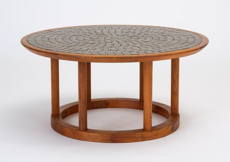 This round Gordon & Jane Martz occasional table has a mosaic top of sage and olive green square tiles in a sunburst formation, set into a solid walnut base. The top is supported by wooden legs rising from a smaller, round pedestal base. Versatile
