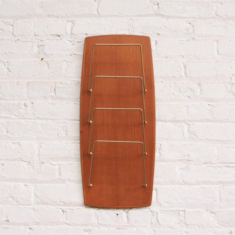 Beautiful wall-mounted midcentury modern magazine rack by Carl Auböck. Teakwood and brass.