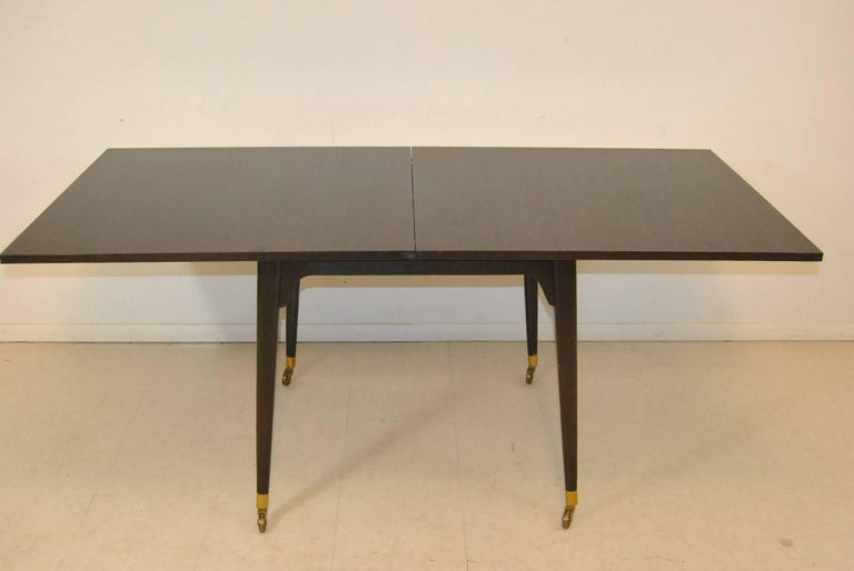 A Mid-Century Modern flip-top game table by Edward Wormley for Dunbar. This fantastic table features heavy brass caster and sleeves, an ebony stain and felt lined storage under the top. The top opens and pivots to make a larger serving surface. Very