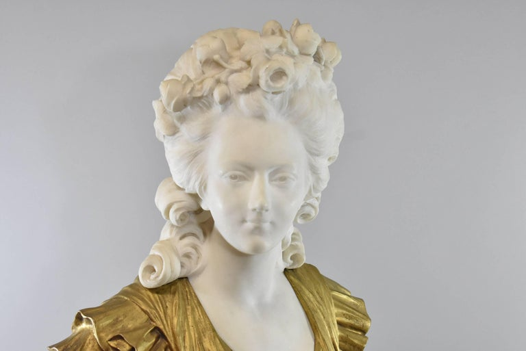 A stunning marble and bronze bust. This beautiful sculpture features a French female with a white marble face with her hair adorned in roses, a gold doré gown and a grey/green marble base. Absolutely exquisite. The dimensions are 28.5