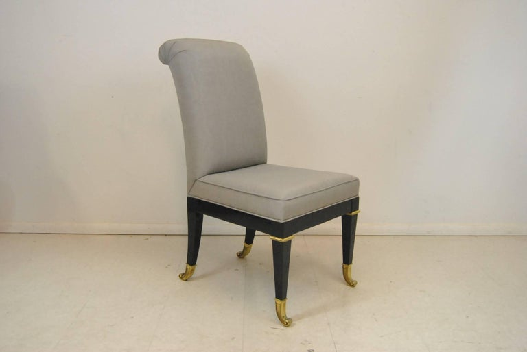 Ten Hollywood Regency style dining chairs in a Classic design from Mastercraft. Unusual brass feet and fittings. Sold as a set that includes eight side chairs and two armchairs - all with ebonized wood finish and brass feet. New upholstery is