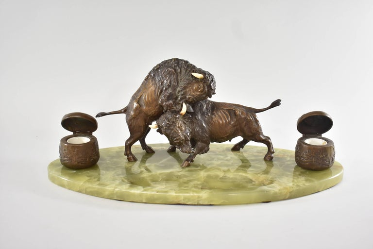 Western inkwell features two cast highly detailed bonze fighting buffalos set on an oval green onyx base with carved out pen rest. The inkwells are embossed with a fenced pastural scene and hold porcelain removable inserts. Nice rich patina.