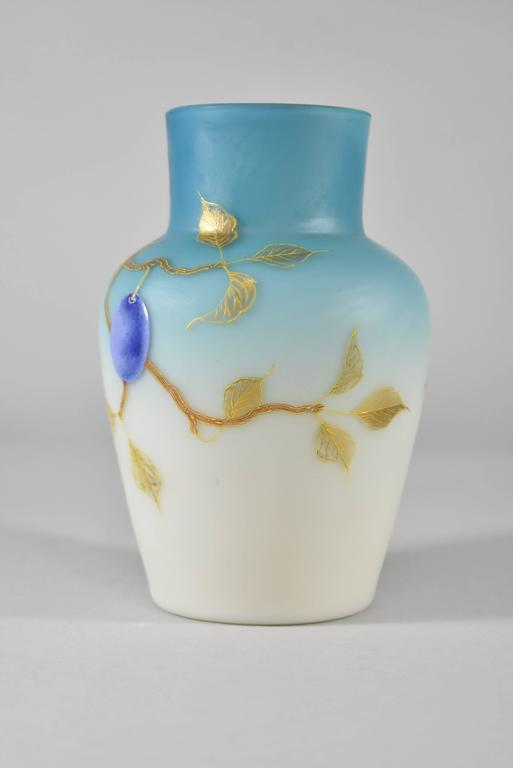 """A beautiful pair of vases by Thomas Webb. These hand-painted vases features plumbs, foliage and branches against a soft blue/white satin background. They are marked on the bottom 676/7, W124 & 5. They are 6"""" T x 4"""" in diameter that"""