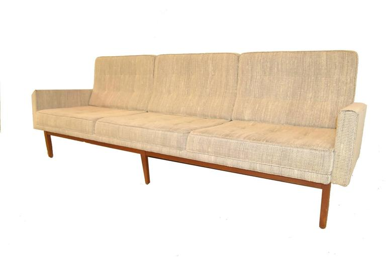 A Classic Mid-Century Knoll model 57W sofa. The floating frame has mortised and pinned construction and is very solid. Original upholstery is in a cream and grey woven fabric with tufted back and seat cushions. Unusual form makes this a highly