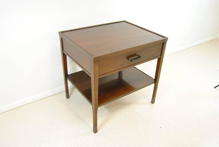 A walnut side table by Bill Sofield for Baker Furniture. This attractive table features antique bronze trim around the bottom shelf and the legs caps. The hardware is wood with bronze and it has dovetailed drawers.